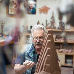 Un ceramista al lavoro inquadrato in maniera piu originale, con elementi fuori fuoco in primo piano che convoglio più rapidamente los guardo sul soggetto